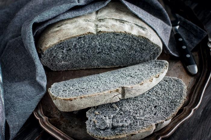 Black coal bread on a metal tray with a gray napkin, chopped, horizontal